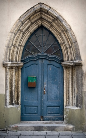 Fragment an ancient build with blue Gothic wooden door photo