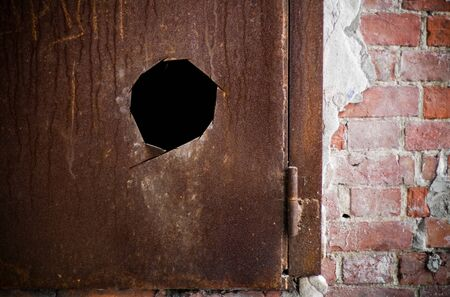 Fragment of a metal rusted door with hole photo