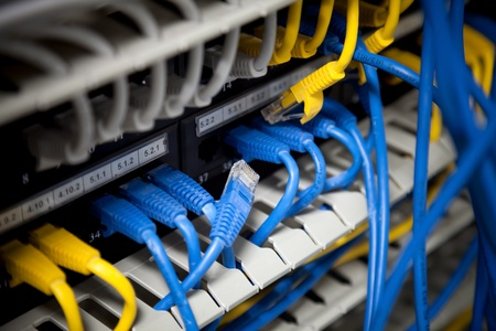 utp: Large network hub and connected blue and yellow cables  Selective focus Stock Photo
