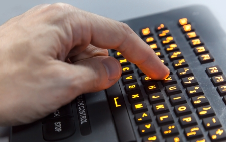 Finger pressing Y key on illuminated industrial keyboard  Selective focus Stock Photo - 15859148