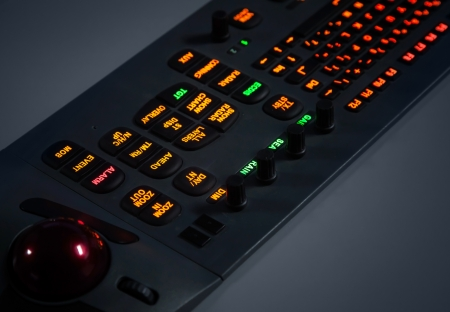 Fragment of colorful illuminated industrial control panel keyboard in the dark  Selective focus photo