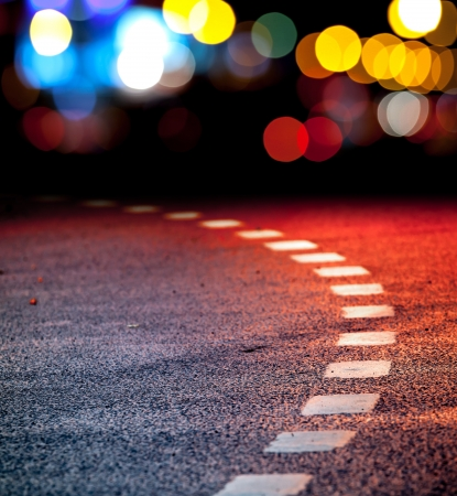 road marking: Turning asphalt road with marking lines and reflections with colorful unfocused lights on a background
