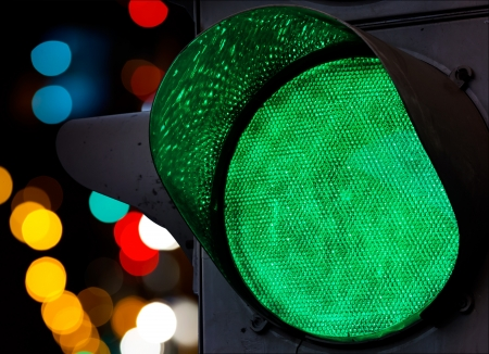 traffic control: Green traffic light with colorful unfocused lights on a background