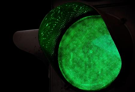 go green background: Green traffic light closeup photo above black background