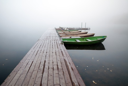 rowboat: Autumn  Small pier with boats on lake in cold still foggy morning