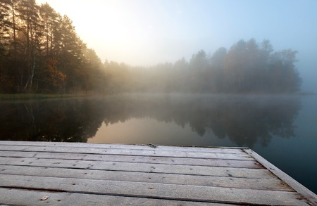Autumnal sunrise  Frozen pier on lake in cold still foggy morning photo