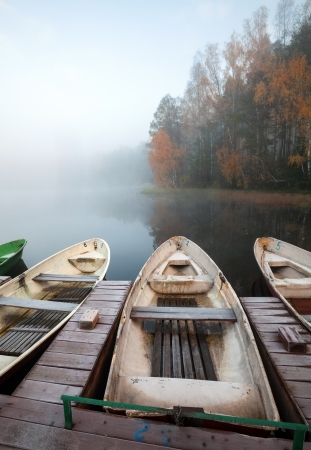 Late autumn foggy morning  Small wooden pier with rowboats on still lake photo