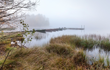 Small pier with boats on lake in cold still foggy morning photo
