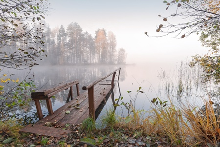 Small wooden pier on still lake in autumn foggy morning photo