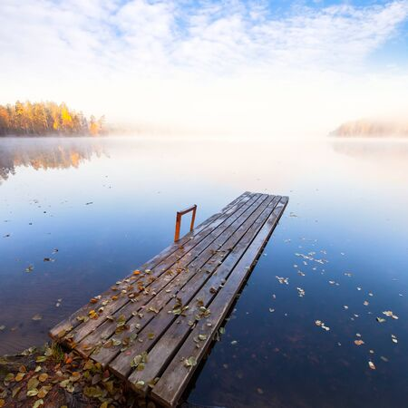 Small wooden pier on still lake in bright autumnal foggy morning photo