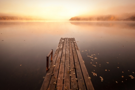 Small wooden pier on still lake in autumnal foggy morning with rising sun photo