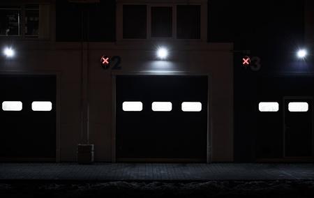 no entrance: Noche textura de fondo de pared moderno edificio de almacenaje con puertas cerradas y las luces