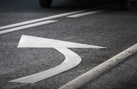 Road marking  White turning arrow and lines on dark asphalt  photo