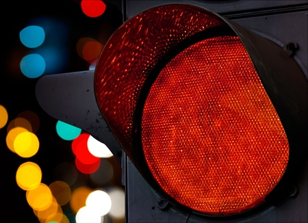 light traces: Red traffic light with colorful unfocused lights on a background