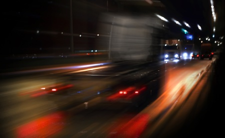 Fast truck driving on the highway with the night lights photo