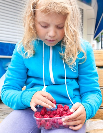 Little blond girl takes raspberry from full plastic box. Outdoor portrait photo