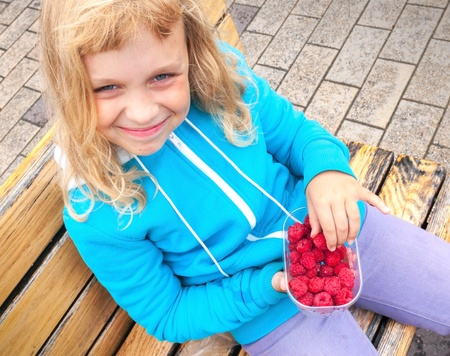 Smiling little blond girl with raspberries in full plastic box. Outdoor portrait photo