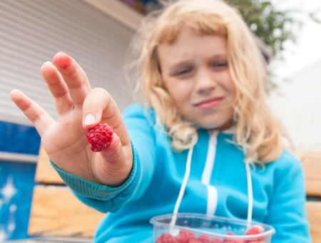 Little blond active girl held out fresh raspberry from his full box. Outdoor portrait with selective focus on berry photo