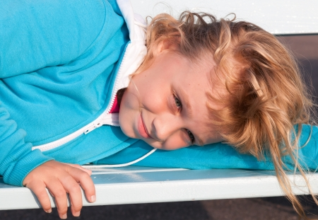 outwear: Little blond girl in casual sport outwear smiles and relaxes on white park bench Stock Photo
