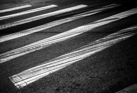 Danger pedestrian crossing with white rectangles and braking tracks on the dark asphalt road photo