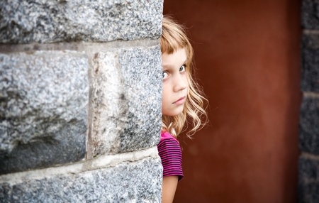 Little blond girl looks out from behind the gray stone wall photo