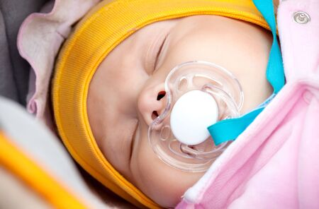 Baby on the walk sleeps with a pacifier photo