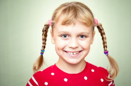 Closeup portrait of smiling little blond girl with pigtails photo