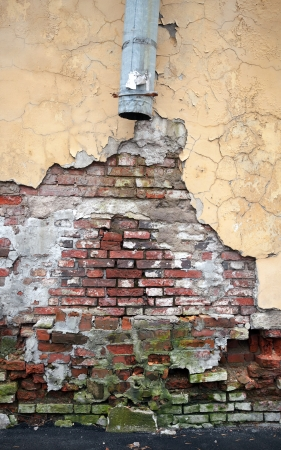 Vintage brick wall texture with damaged plaster and broken drainpipe Imagens
