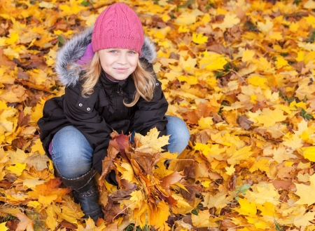 Little blond girl seat on the park ground with yellow autumn leaves  Outdoor smiling portrait photo