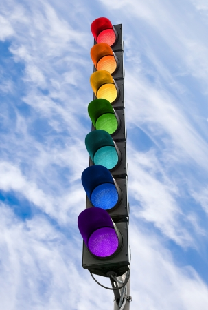 Seven-color rainbow scheme traffic light concept above blue sky