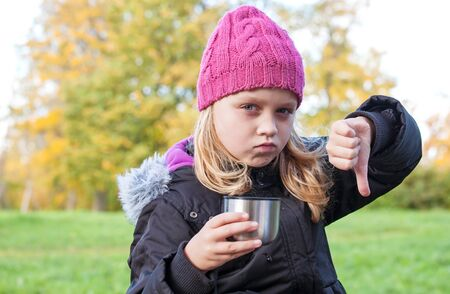 little beautiful blond girl drinks tea in autumnal park and showing thumbs down photo