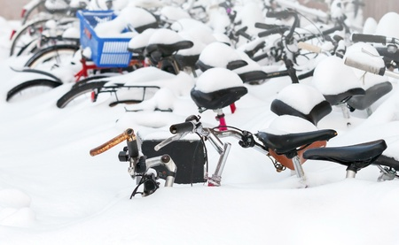 European city winter fragment  Bicycles covered with snow in big snowdrift photo