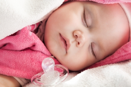 soother: Baby girl sleeps in pink and white cotton towels with a pacifier nearby;