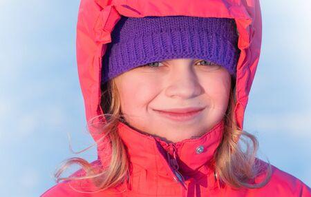 outwear: little ruddy nice girl in winter outwear with hood smiles