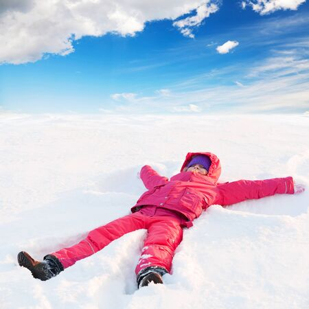 outwear: little ruddy nice girl in winter outwear with hood lies in snow and smiles