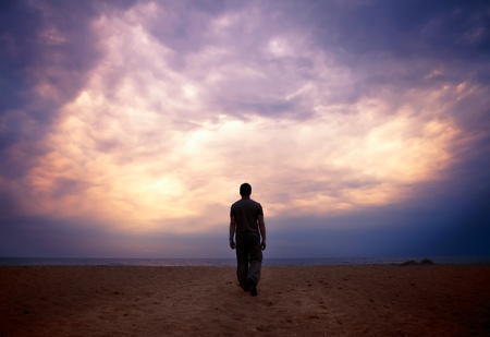 Man goes to the sea on dark sand beach under beautiful colorful cloudy sky photo