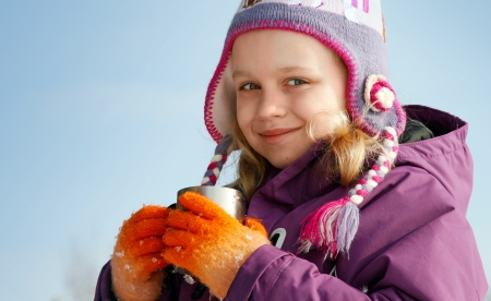 outwear: Smiling little blond girl in cold season wears winter outwear with metal thermos cup of hot tea
