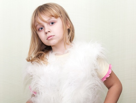 Little blond girl wears white fluffy fur vest photo