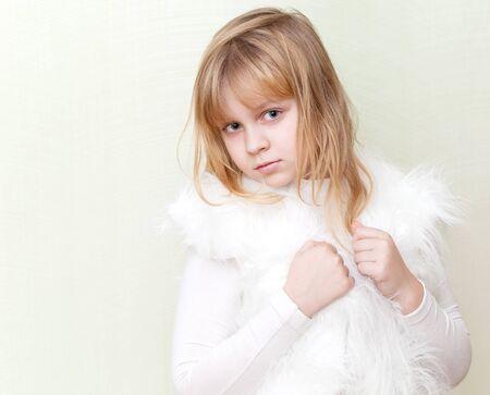 Little blond girl in white fluffy fur vest photo