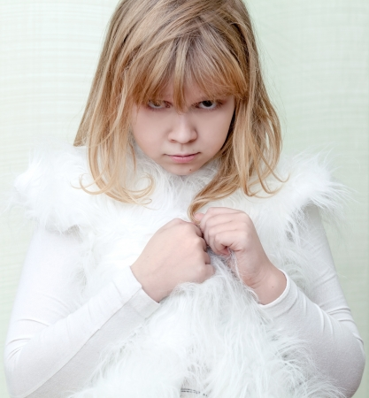 Little angry blond girl wears white fluffy fur vest photo