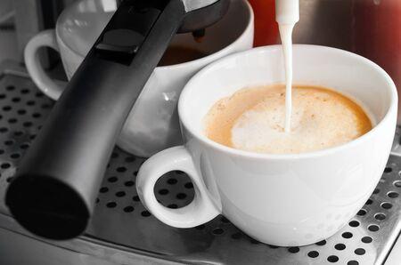 capuchino: Coffee maker pouring hot milk in white cup to prepare cappuccino