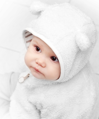 baby girl playing: little baby in white bear costume on white background Stock Photo