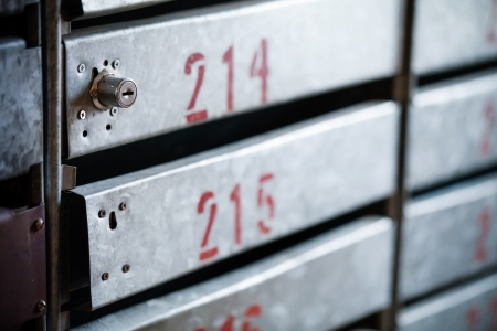 Old iron postboxes with locks and red apartment numbers photo