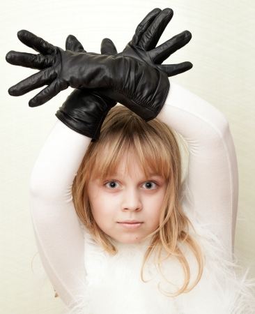 Little blond girl shows a deer with antlers as a gloves photo