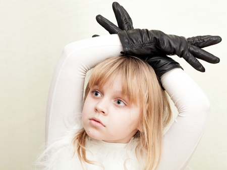 Little blond girl shows a deer with antlers as a black gloves photo