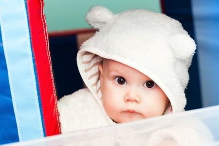 little baby in white bear costume looks through the window on a playground photo