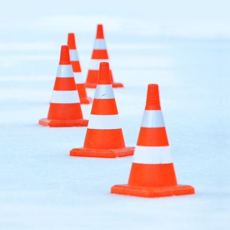 Red and white striped cones on the ice photo