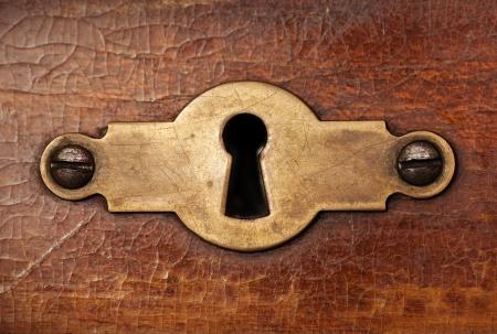 to lock: Vintage elemento in rame buco della serratura decorativo su weathered superficie in legno