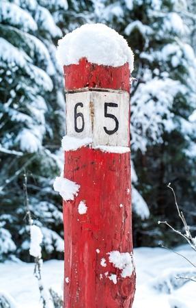 chilometro: Old subito rosso segno di legno km con neve sulla strada forestale