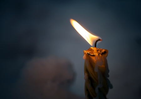 Closeup photo of little candle flame in the dark photo